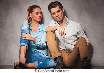 young casual woman looks at her boyfriend while sitting together