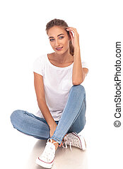 young casual woman sitting with hand on head