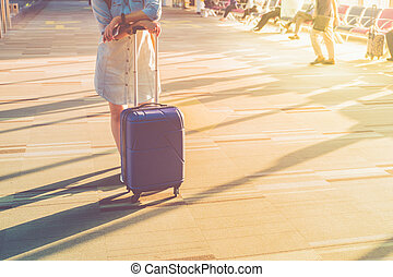 Young casual woman wear white sneakers standing with travel suitcase with morning sunlight through window at airport terminal,Vacation concept.