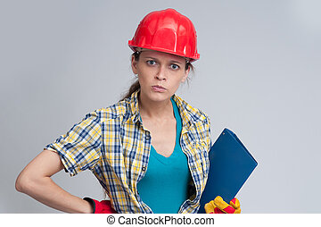 Young casual woman wearing safety helmet. Isolated on gray