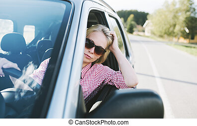 Young caucasian blond woman traveling by car and having fun on her summer holiday journey. Happy girl driving car on countryside road.