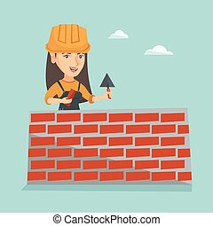 Young caucasian bricklayer building a brick wall.