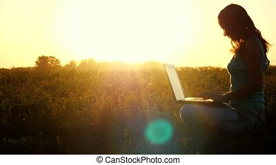 Young caucasian brunette woman typing on a laptop outdoors at beautiful sunset sitting on the grass with amazing lense flare effects in summer time. 3840x2160