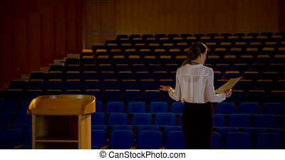 Young Caucasian businesswoman practicing speech in empty ...