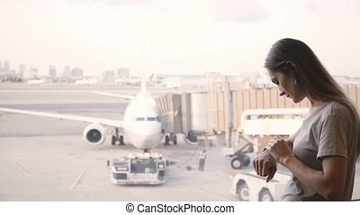 Young Caucasian businesswoman standing at airport terminal lounge window using smart watch, looking at airplanes.