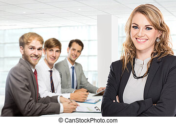Young caucasian businesswoman, with her team behind