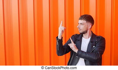 Young caucasian cheerful brunette man in black leather jacket is dancing on orange background, close-up, slow motion, prance