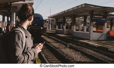 Young Caucasian commuter girl using smartphone social network at railway station, modern train coming up to the platform