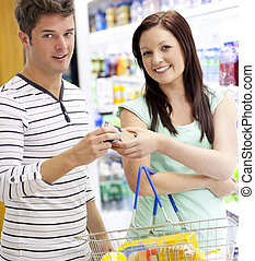 Young caucasian couple buying shampoo standing in a department of a supermarket