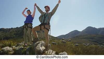 Young Caucasian couple holding hands in zip lining equipment...