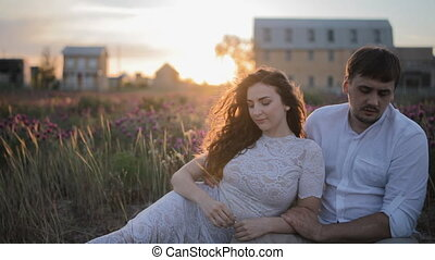 Young caucasian couple sit in the field