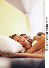 Young caucasian couple sleeping on bed