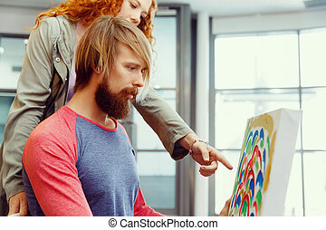 Young caucasian couple standing in a gallery and contemplating artwork