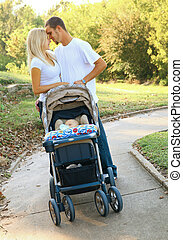 Young Caucasian Couple Taking Their Baby On Walk