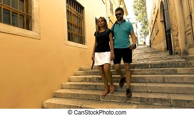 Young caucasian couple walking down pedestrian Mediterranean town street on vacation