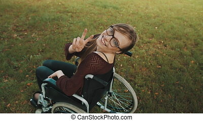 Young caucasian disabled brunette woman looking overshoulder with peace fingers gesture. High quality 4k footage
