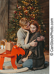 Young caucasian family mom dad son near fireplace christmas tree