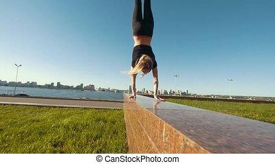 Young caucasian female cheerleader walking on handstand...