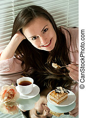Young Caucasian female sitting at a table on a light ...