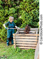 Young caucasian female tumbling the compost with a pitch fork