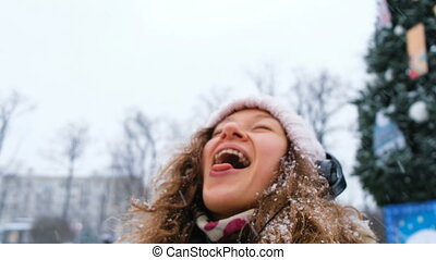 Young caucasian girl catches snowflakes with his mouth in a Park with headphones closeup.