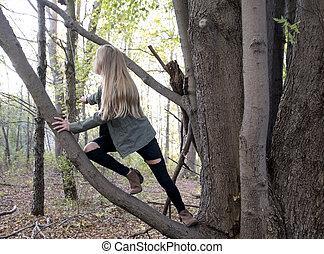 young Caucasian girl climbing tree