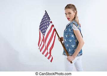 young caucasian girl looking at camera and waving USA flag, Independence Day Celebration