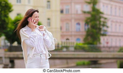 Young caucasian girl talking by her smartphone outdoor at european city. Beautiful girl on the street using smartphone and talking by phone with her friend