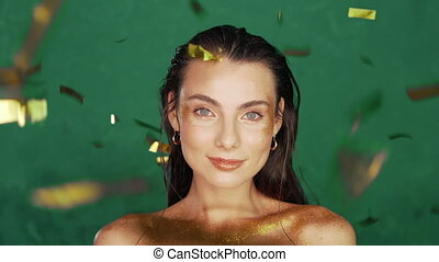 Young caucasian girl with long hair and art golden visage having fun in confetti rain on green background. Woman celebrating, depicts joy and happiness. Success, party, holiday concept