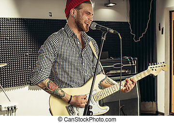 young caucasian guitarist contemporaneously play guitar and sing a song in recording studio. handsome guy in red hat emotionally sing song, keen on music