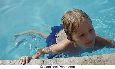 Young Caucasian joyful boy having fun on vacation in the pool in slow motion. 1920x1080