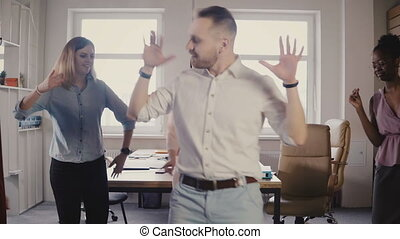 Young Caucasian male executive doing a funny victory dance...