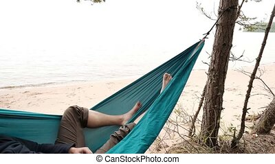 Young caucasian male resting lying on blue hammock outdoors...