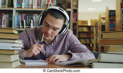 Young caucasian male student with big headphones is sitting...