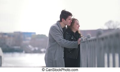 Young caucasian man and woman walking hugged in a windy day