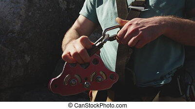 Young Caucasian man fastening zip lining harness - Close up ...