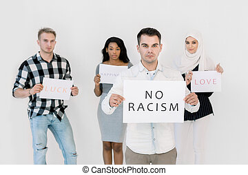 Young Caucasian man holding No racism sign, three multiethnical friends activists holding social slogans, love, happiness, standing isolated on the white background.