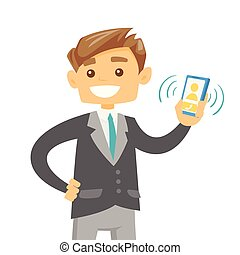 Young caucasian man holding ringing mobile phone. - Young...
