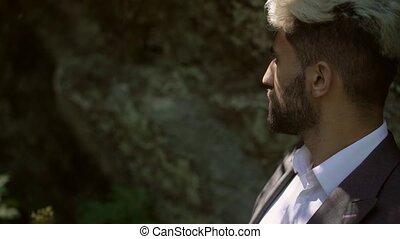 Young caucasian man in classical suit posing near rock