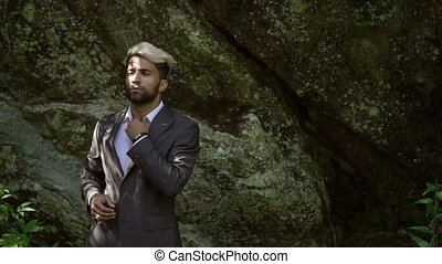 Young caucasian man in classical suit posing near rock