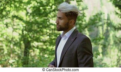 Young caucasian man in classical suit posing steadicam