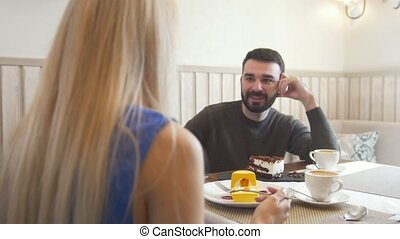 Young caucasian man in front of woman talking in the cafe and looking each other, close up