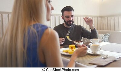 Young caucasian man in front of woman tries desserts in the...