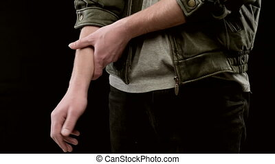 Young caucasian man in leather jacket, rubs hand. Close-up ...