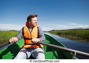 Young caucasian man paddles in a boat resting on the lake.
