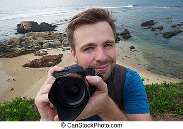 young caucasian man photographer with photo camera on summer holiday and vacation travel