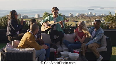 Young Caucasian man playing guitar on a rooftop with his ...