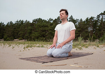 Young caucasian man preparing for yoga practice on the beach