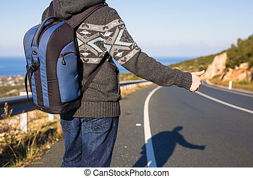 Young caucasian man seen from behind carrying a backpack...