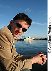 Young caucasian man sitting on a pier